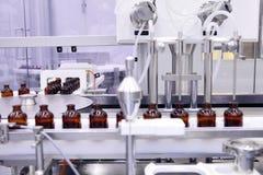 射入的不育的胶囊 在配药植物的装瓶专线的瓶 机器在检查不育的液体以后 库存照片