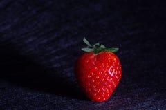 射出它的阴影的草莓隔绝在与黑纹理的背景中 免版税库存图片