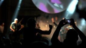 射击一些欢呼扇动在生活音乐会,慢动作 音乐会就座在肩膀和举的她的手女孩 影视素材