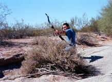 射击一把折回弓的传统阿切尔在沙漠 免版税图库摄影