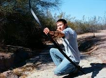 射击一把长的弓的传统阿切尔在沙漠 免版税库存图片