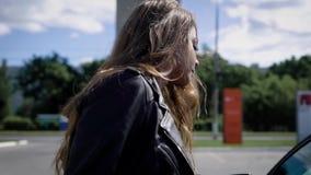 射击从走到她的在停车场的汽车的后面一名白肤金发的妇女 股票录像
