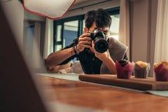 射击在他的演播室的食物摄影师 免版税库存图片