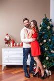 射击在庆祝圣诞节的爱的一对年轻愉快的夫妇 免版税库存照片