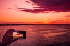 射击在智能手机的日落 库存图片