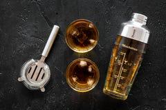 射击威士忌酒有冰和男服务员设备黑色桌背景顶视图 图库摄影