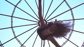 射击杂技演员在暂停的圆环的天空中转动的女孩的慢动作 股票录像