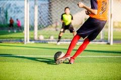射击球的足球运动员奔跑在点球对目标有模糊的守门员背景 免版税图库摄影