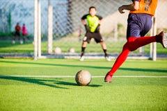 射击球的足球运动员奔跑在点球对目标有模糊的守门员背景 免版税库存图片