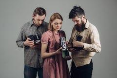 射击聪明的学校 减速火箭的样式妇女和人拿着模式照片照相机 无固定职业的摄影师或摄影记者有老葡萄酒的 库存照片