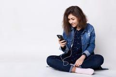 射击可爱的女孩佩带的斜纹布夹克和牛仔裤坐在地板盘的腿放松了有耳机在她的耳朵bei 库存图片