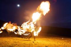 射击展示,跳舞与火焰,男性主要骗子吹的火,表现户外,火焰控制与火的人舞蹈 免版税库存照片
