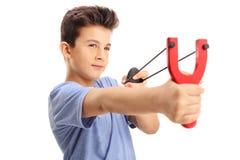 射击从弹弓的小男孩一个岩石 免版税图库摄影