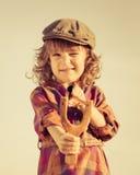 射击木弹弓的滑稽的孩子 免版税库存照片