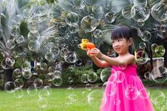 射击从泡影吹风机的亚裔矮小的中国女孩泡影 库存照片