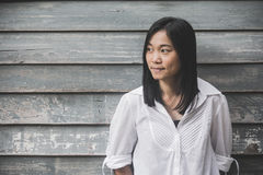 射击照片亚洲妇女画象穿戴白色衬衣和看斜向一边有木墙壁背景 库存照片