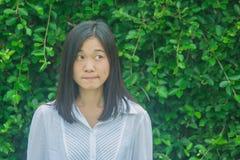 射击照片亚洲妇女画象穿戴白色衬衣,认为和看斜向一边有绿色树背景 免版税图库摄影