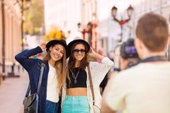射击他们的女孩微笑和人与照相机 免版税图库摄影
