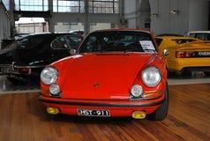 射击红色保时捷911 Carrera汽车,在显示的老经典减速火箭的模型购买的 免版税库存照片