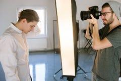 射击英俊的模型的摄影师 免版税库存图片