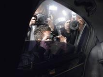 射击通过车窗的无固定职业的摄影师 免版税库存图片