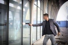 射击a的年轻探员或警察或者流氓 免版税库存图片