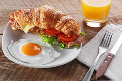 将与煎烟肉乳酪蕃茄早餐和鸡蛋的新月形面包夹在中间 免版税库存图片