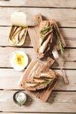 将塔帕纤维布夹在中间用沙丁鱼、西鲱橄榄和盐 库存照片