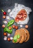 将成份夹在中间用熏制的肉、菜和沙拉叶子在黑暗的背景 库存图片