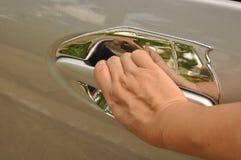 将打开车门妇女的手 免版税库存照片