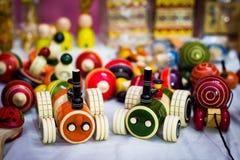 将扯拽的橙色和绿色木路轨罗伊汽车与螺纹 葡萄酒木玩具 免版税库存照片