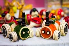 将扯拽的橙色和绿色木路轨罗伊汽车与螺纹 葡萄酒木玩具 库存照片