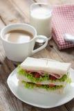 将火腿夹在中间用乳酪、咖啡和牛奶在木桌上 免版税图库摄影