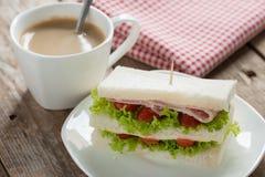将火腿夹在中间用乳酪和咖啡在木桌上 图库摄影