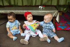 小三个孩子:黑人美国,白种人男孩和俄国选址的女婴  免版税图库摄影
