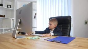 小上司和秘书 衣服的快乐的小男孩发布命令,当站立在他附近时的formalwear的小女孩 免版税库存照片