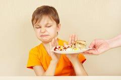 小不满的男孩拒绝吃与鱼圆的面团 免版税库存照片