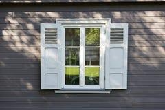小与快门的葡萄酒白色窗口在木灰色墙壁上 库存图片