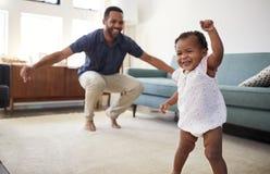 小与父亲的女儿跳舞在休息室在家 免版税图库摄影