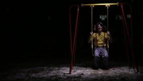 小丑乘坐在黑暗的低儿童摇摆 股票视频