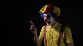 小丑使用一个智能手机叫观察者 股票录像