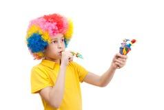 小丑假发的男孩与木玩具和口哨 库存图片