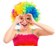 小丑假发的逗人喜爱的女孩使用她的作为双筒望远镜的手 免版税图库摄影