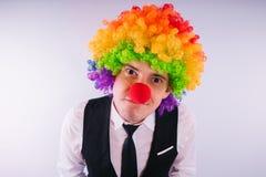 小丑假发的,小丑概念办公室工作者在工作 与小丑假发的商人在白色 免版税库存照片
