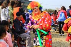 小丑做一个小男孩的一个Baloon动物 免版税图库摄影