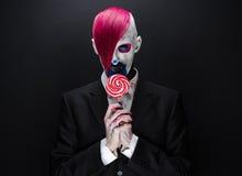 小丑和万圣夜题材:有桃红色头发的可怕小丑在一件黑夹克用糖果在手中在黑暗的背景在演播室 免版税库存照片