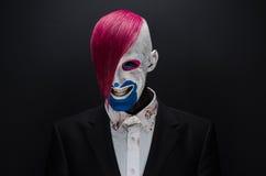 小丑和万圣夜题材:有桃红色头发的可怕小丑在一件黑夹克用糖果在手中在黑暗的背景在演播室 免版税图库摄影