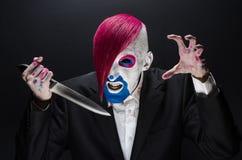 小丑和万圣夜题材:有桃红色头发的可怕小丑在一件黑夹克用糖果在手中在黑暗的背景在演播室 库存照片