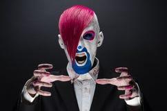 小丑和万圣夜题材:有桃红色头发的可怕小丑在一件黑夹克用糖果在手中在黑暗的背景在演播室 库存图片