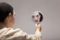 小丑坐与一个镜子的地面在他的手上 免版税库存图片